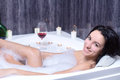 Woman takes bath a beautiful in a with foam drinking wine Royalty Free Stock Image