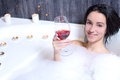 Woman takes bath a beautiful in a with foam drinking wine Stock Photography