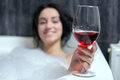 Woman takes bath a beautiful in a with foam drinking wine Royalty Free Stock Photo