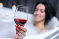 Woman takes bath a beautiful in a with foam drinking wine Stock Image
