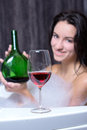 Woman takes bath a beautiful in a with foam drinking wine Royalty Free Stock Photos