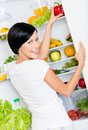 Woman takes bell pepper from opened refrigerator the full of vegetables and fruit concept of healthy and dieting food Stock Photography