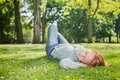 Woman takes a nap in a park lies down for on green grass or nature Royalty Free Stock Photography