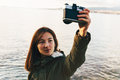 Woman takes photographs self portrait on coastline traveler smiling young with old photo camera background of sea Stock Image