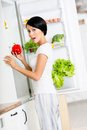 Woman takes sweet pepper from opened fridge the full of vegetables and fruit concept of healthy and dieting food Royalty Free Stock Image