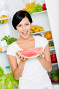 Woman takes watermelon from opened fridge the full of vegetables and fruit concept of healthy and dieting food Stock Images