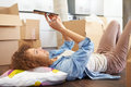 Woman taking a break with digital tablet in new home lying down on floor Stock Image