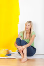 Woman taking a break from painting laughing casual barefoot young sitting on the floor with half painted yellow and white wall Stock Image