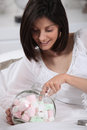 Woman taking marshmallow brunette with her hand in the jar Stock Photo