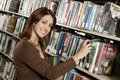 Woman Taking Out Book From Bookshelf Stock Image