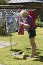 Woman taking pegs from a peg bag to hang washing Royalty Free Stock Photo