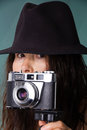 Woman taking a photo with hat takes photos with old camera Stock Photo