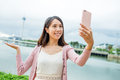 Woman taking photo by herself with mobile phone in Macao city Royalty Free Stock Photo