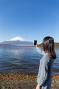Woman taking photo with mobile phone on Fujisan Royalty Free Stock Photo