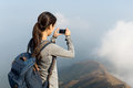 Woman taking photo at the top of the hill Royalty Free Stock Photo