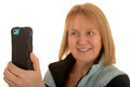 Woman taking photograph mobile phone in dark protective case being used by smiling blonde to take a white background Royalty Free Stock Photos