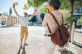 Woman taking photos of an excited senior man men in the city mature couple enjoying themselves on a vacation Royalty Free Stock Photo