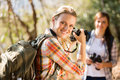 Woman taking photos friend pretty young women of her in autumn mountain Royalty Free Stock Photography
