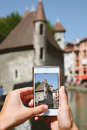 Woman taking photos with mobile phone in annecy streets france Royalty Free Stock Photography