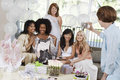 Woman taking pictures of friends at bridal shower middle aged women Stock Photo