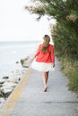 Woman taking a relaxing walk at the sea barefoot walking away from camera along walkway above ocean Stock Photos