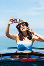 Woman taking selfie photo on car summer vacation happy smartphone travel to the coast brunette girl leaning out sunroof with Stock Images