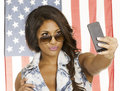 Woman taking a selfie self portrait with phone young of herself for social networking the american flag behind her lifestyle Royalty Free Stock Images