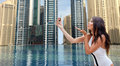 Woman taking selfie with smartphone over city pool Royalty Free Stock Photo