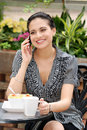 Woman talking on cell phone in outdoor cafe Stock Photo