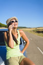 Woman talking on cellphone during summer car travel happy call enjoying vacation female traveler roadtrip in spain Stock Photos
