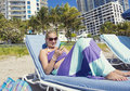 Woman talking on her cell phone while lounging on the beach Royalty Free Stock Photo
