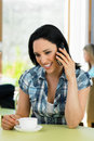 Woman talking on mobile phone in cafe smiling Stock Photo