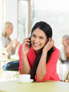 Woman talking on mobile phone in cafe smiling to camera Royalty Free Stock Image