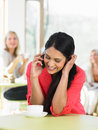 Woman talking on mobile phone in cafe smiling to camera Royalty Free Stock Photos