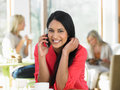 Woman talking on mobile phone in cafe smiling to camera Stock Photography