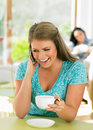 Woman talking on mobile phone in cafe using and laptop smiling Stock Photos