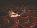 Woman talking on phone in auditorium Royalty Free Stock Photo