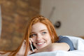 Woman talking on the phone in bed Royalty Free Stock Photo