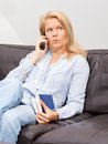 Woman talking on the phone at home a beautiful blond is sitting a couch into having a conversation Royalty Free Stock Photography