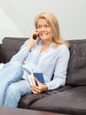 Woman talking on the phone at home a beautiful blond is sitting a couch into having a conversation Stock Image