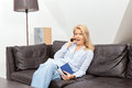 Woman talking on the phone at home a beautiful blond is sitting a couch into having a conversation she looks very surprised Royalty Free Stock Image