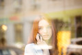 Woman talking on the phone and looking in window portrait of a redhead Stock Photo