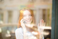 Woman talking on the phone and looking at window portrait of a smiling redhead waving palm to somebody Royalty Free Stock Photography
