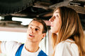 Woman talking to car mechanic in repair shop Royalty Free Stock Photo