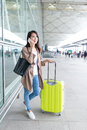 Woman talking to cellphone with luggage in airport Royalty Free Stock Photo