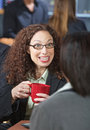 Woman talking to friend happy business with red mug Stock Photography