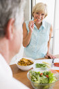 Woman Talking To Husband As She Prepares A meal Royalty Free Stock Images
