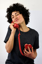 Woman talks on red phone is talking the which is connected to her heart in a conceptual image Royalty Free Stock Image