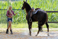Woman taming a horse beautiful blond cowgirl trying to tame brown Stock Images