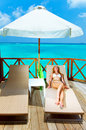Woman tans on a terrace of water villa on ocean Stock Photo